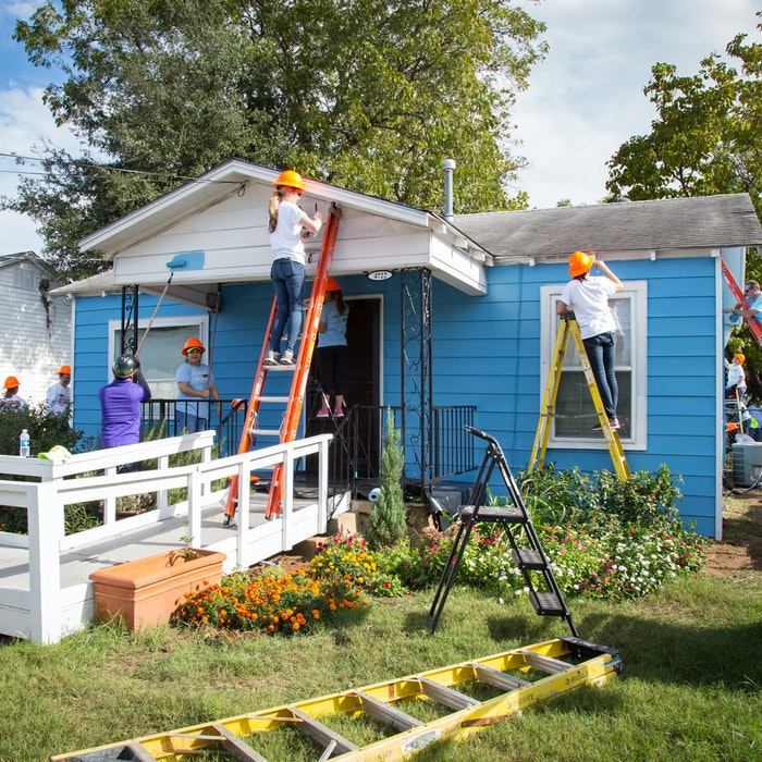 volunteers painting the exterior of a house