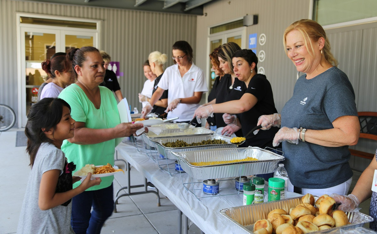 volunteers serve food to families