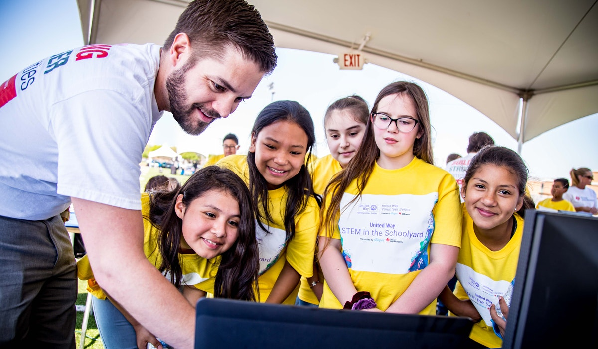 volunteer showing group of kids something on a computer
