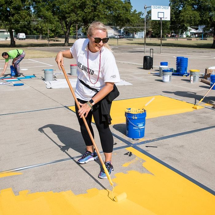 volunteer in LIVE UNITED shirt updating playground