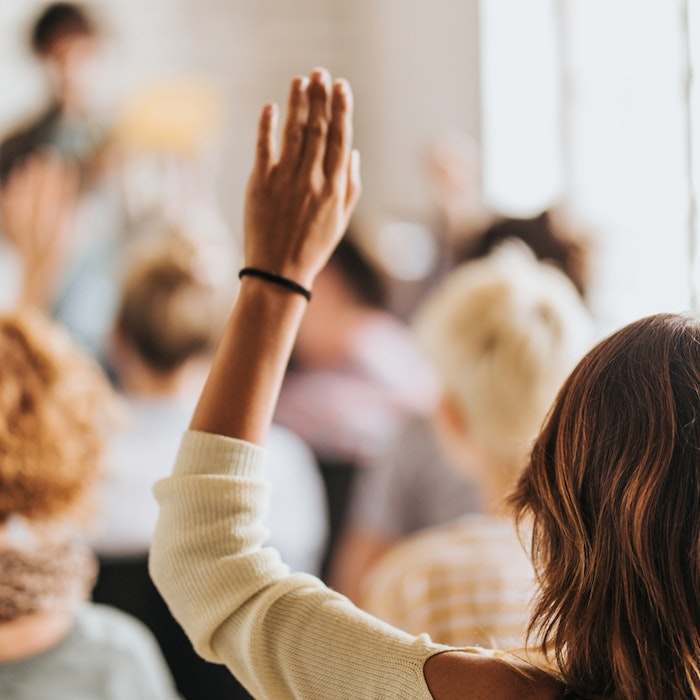 photo of back of woman's head/hand raised in a classroom