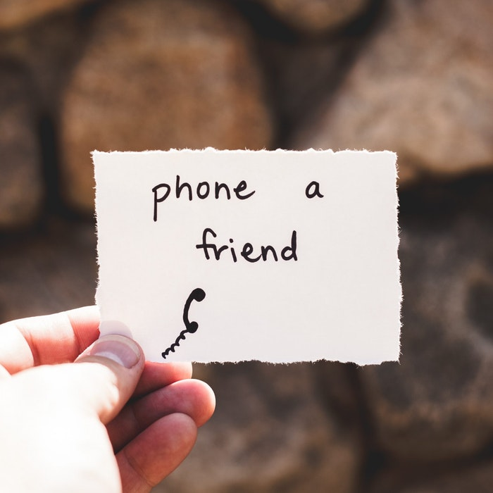 hand holding a paper, phone a friend