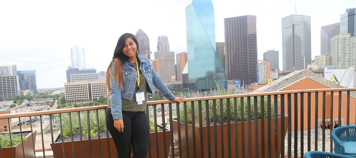teen girl on patio with Dallas cityscape behind