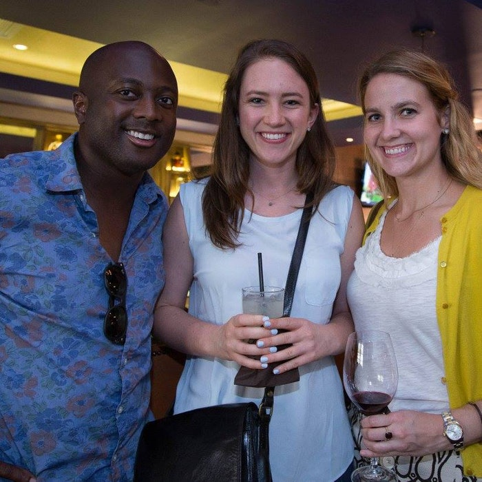 three young adults with drinks smile