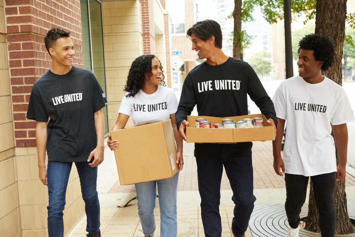 young adults volunteering carry canned goods