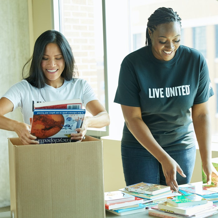 two women volunteers pack books in boxes