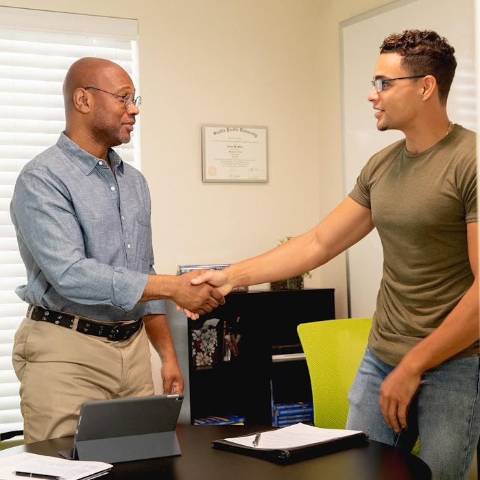 two gentleman shake hands in office