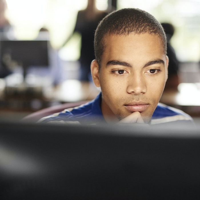 young man stares intently at computer