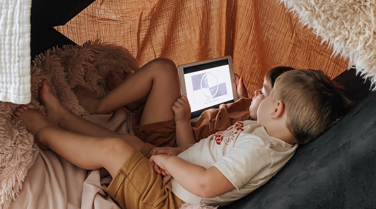 two kids under a fort reading a book via Vooks