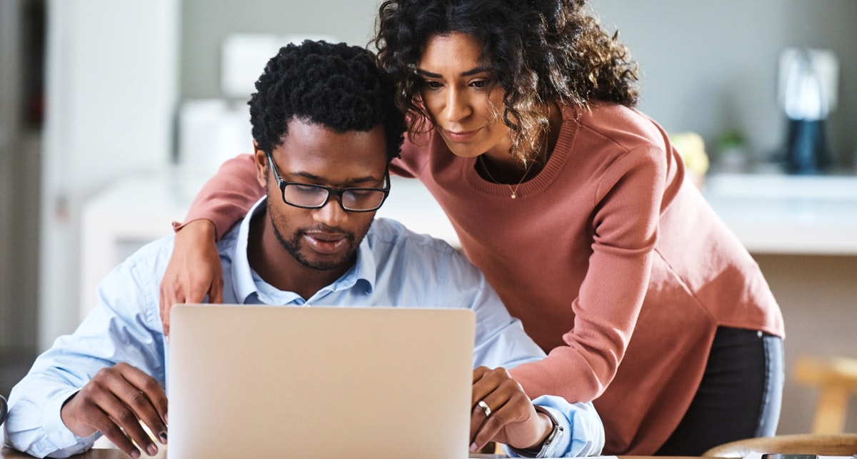 black couple on computer applying for financial assistance